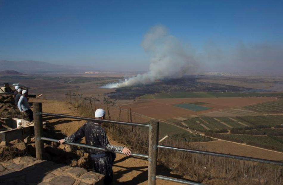 Druze men look at smoke rising on the Israeli-controlled side of the line dividing the Israeli...