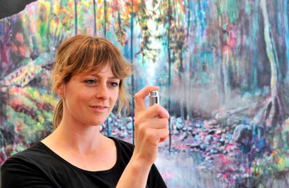 Dunedin artist Anya Sinclair (36) sprays the perfume that inspired  the Never & Forever piece...