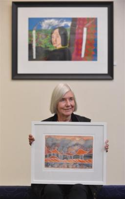 Dunedin artist Marilynn Webb holds one of her works, while a Jeffrey Harris painting is pictured...