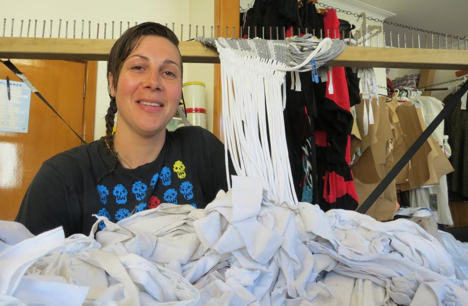 Dunedin fashion designer Fiona Clements examines T-shirt strips she will weave into a korowai to...