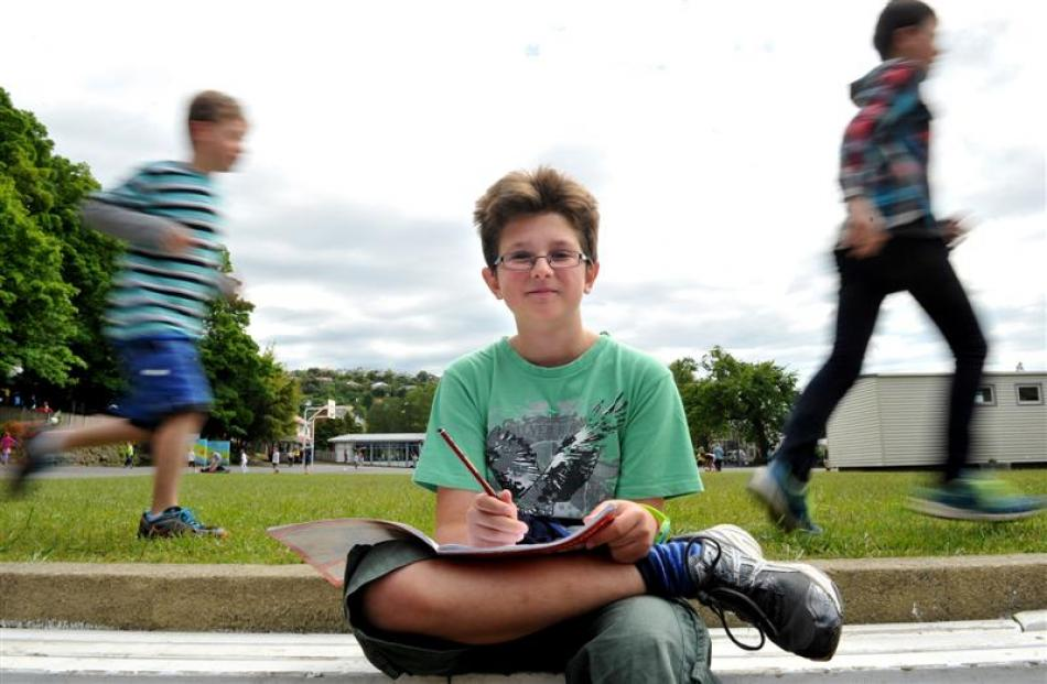 Dunedin George Street Normal School pupil Jasper Seddon contemplates his next story while his...
