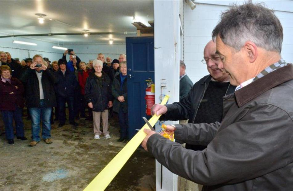 Dunedin Mayor Dave Cull cuts the ribbon to open the new Taieri Blokes' Shed with founding member...