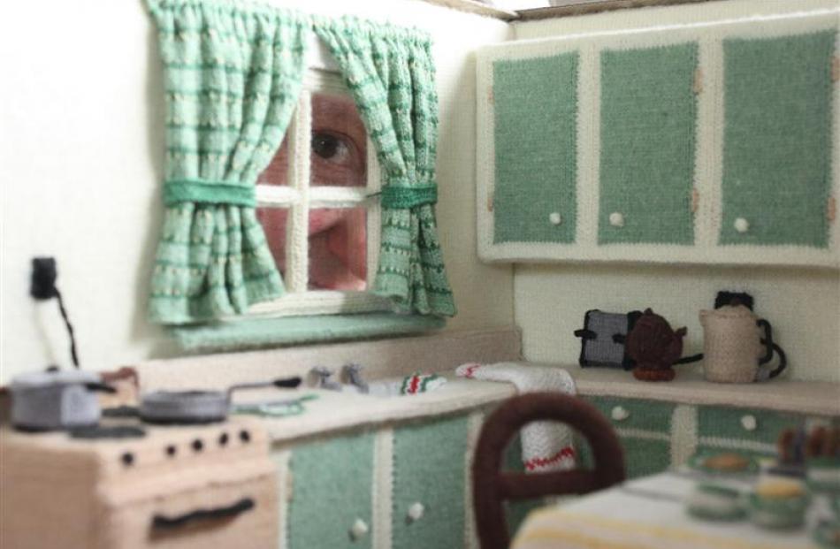 Dunedin Miniaturist Club member Jill York looks through the window of the miniature kitchen she...