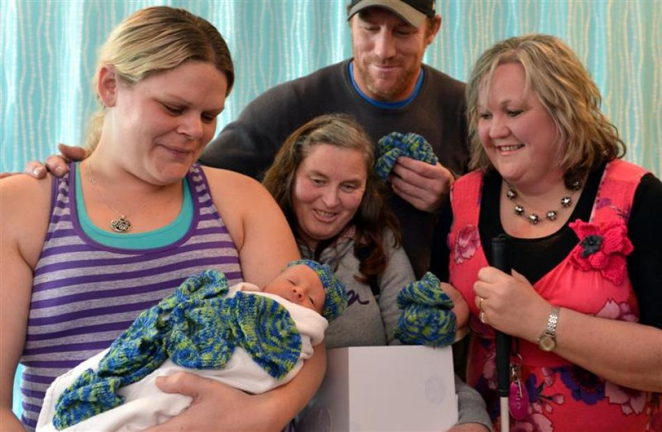 Dunedin mother Kristy Tennison tries a beanie for size on week-old Kaleb Moodie, watched by (from...