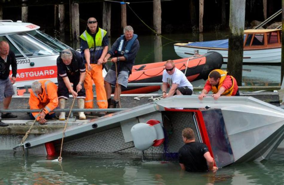 Eight men attempt to right a boat which overturned a second time, at Back Beach, Port Chalmers,...