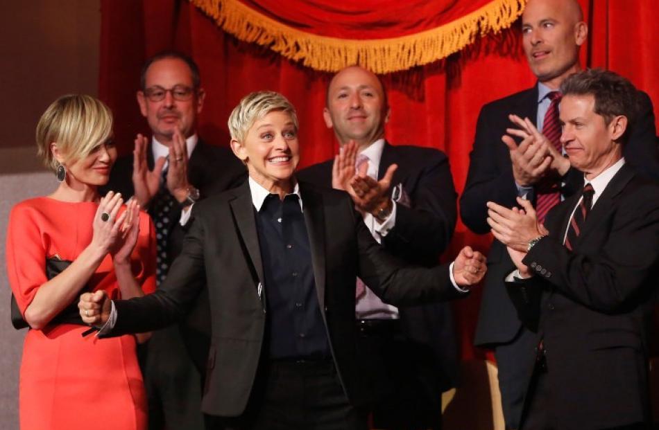 Ellen DeGeneres (C) smiles as family and friends, including wife Portia de Rossi (left), applaud...