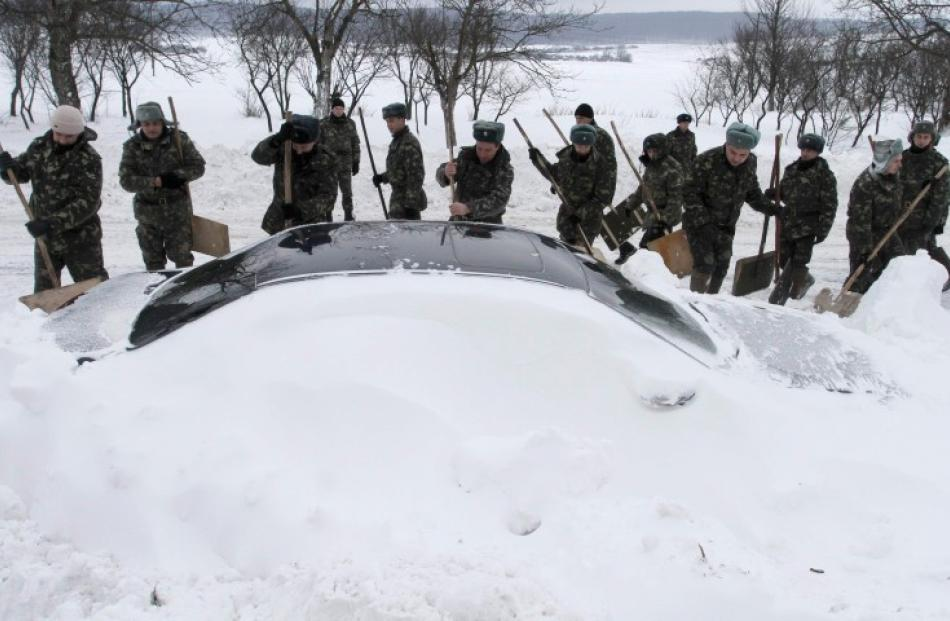 Emergency workers remove snow from around a car trapped in snow, after blizzards near the western...