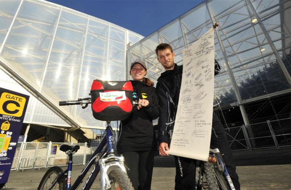 "England rugby fans Jodie Burton and Tom Hudson show their ""World in Union"" scroll outside Otago..."