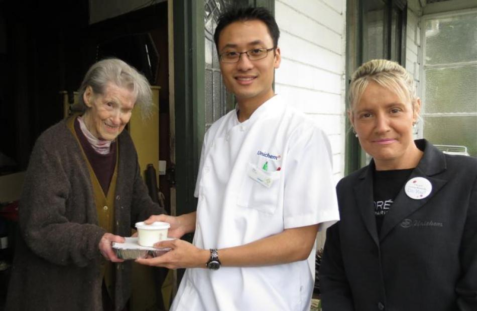 Enid Ford (left)  receives a meal from  Unichem Knox Pharmacy's dispensing manager Shin wei Chan ...