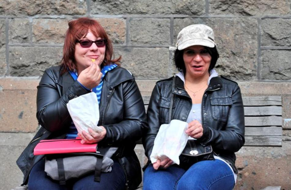 Enjoying some chips outside the Dunedin Law Courts yesterday are Pacific Pearl passengers Jackie...