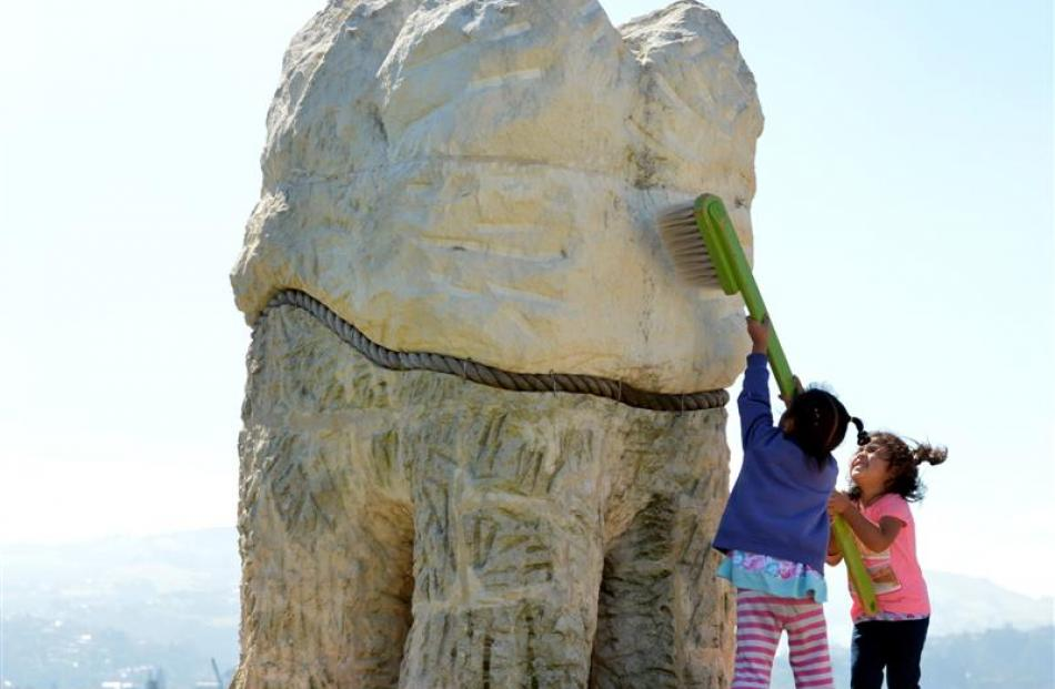 Esther Halalilo (4, left) and Manusiu Pole (3) take a big toothbrush to one of the Harbour Mouth...