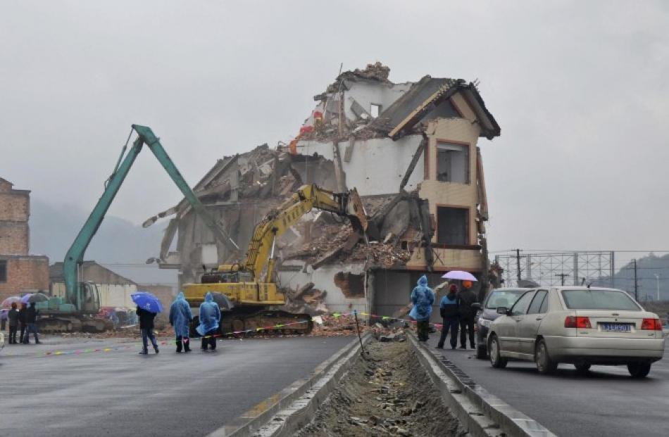 Excavators demolish the house of Luo Baogen in the middle of a newly built road in Wenling,...