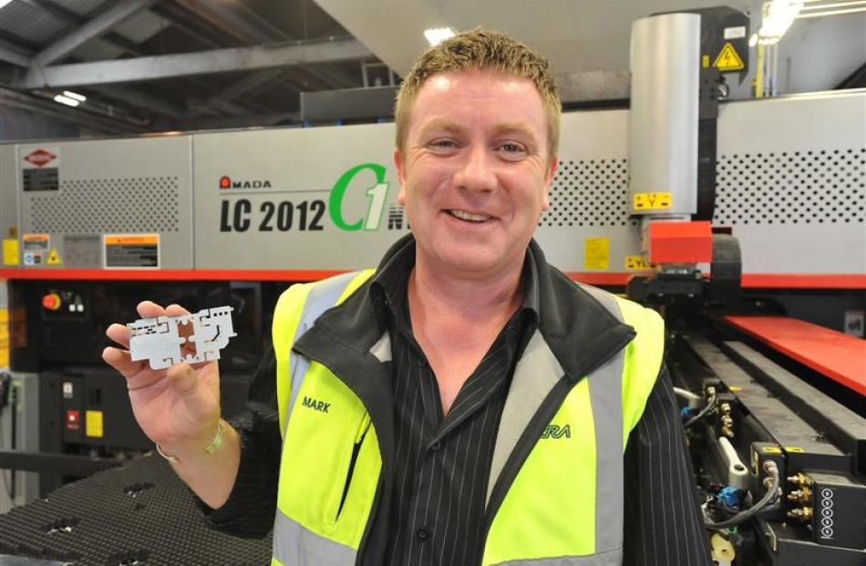 Farra Engineering's sheet metal division manager, Mark Stewart, holds a small laser-cut part....