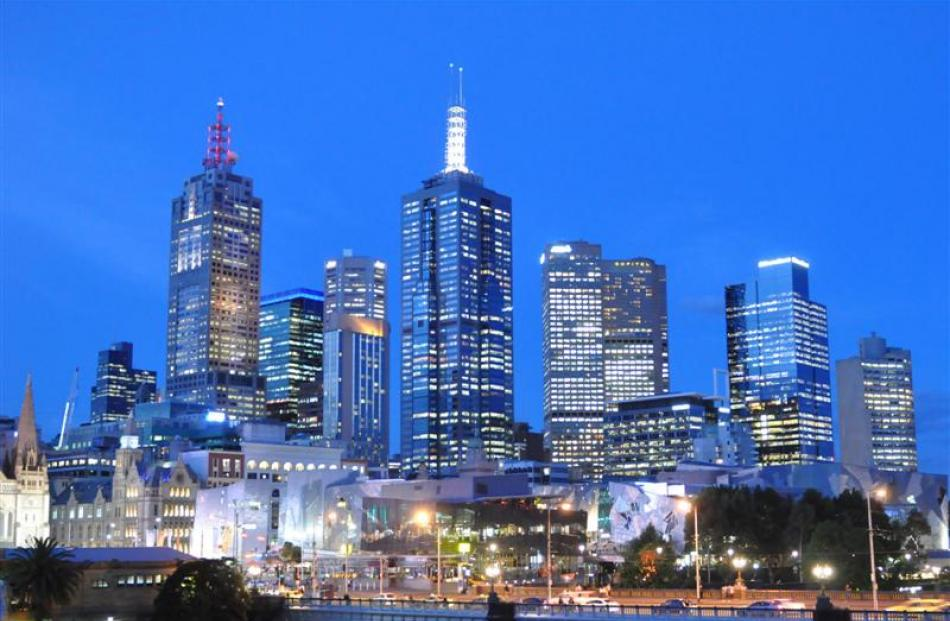Federation Square and high-rise buildings light the twilight sky in downtown Melbourne. Photo by...