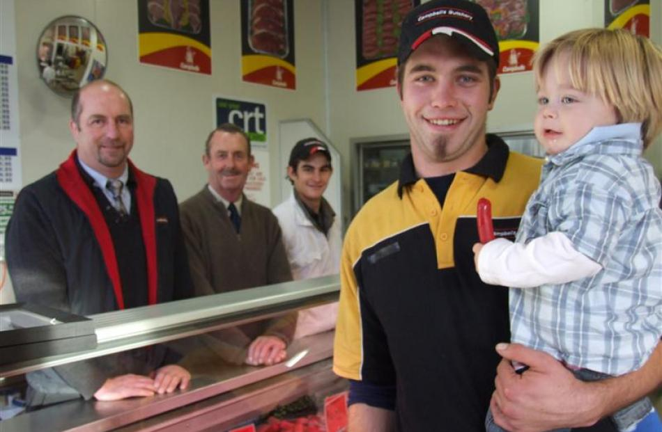 Fifth-generation butcher Jason Campbell holds his son Rayffe at Campbells Butchery, watched by ...