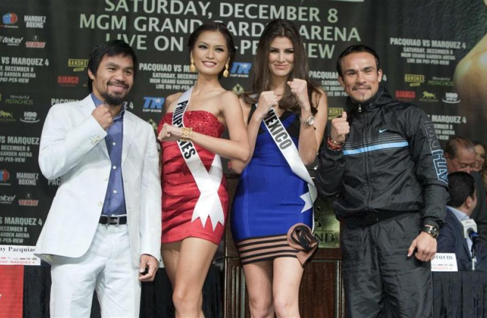 Filipino boxer Manny Pacquiao (left) and Juan Manuel Marquez, of Mexico, pose with Miss Universe...