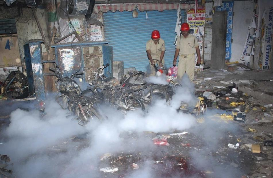 Fire fighters extinguish a fire at the site of an explosion in the southern Indian city of...
