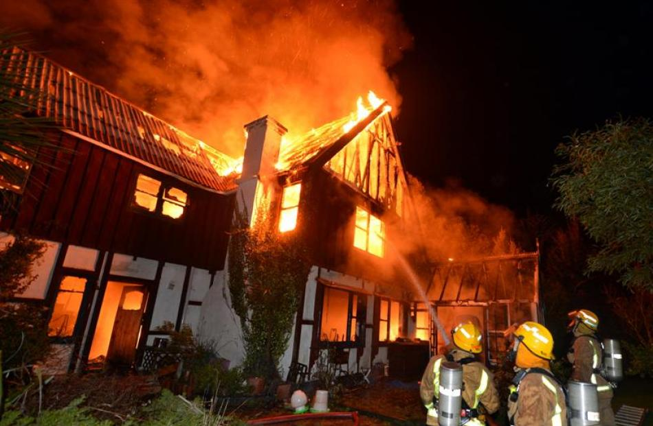 Firefighters battle a house fire in St Leonards Dr, Dunedin, about 3am yesterday. The window from...