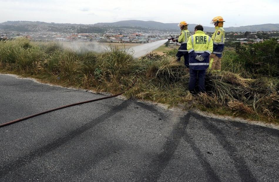 Firefighters extinguish a grass fire believed started by sparks caused by a car doing a burnout...