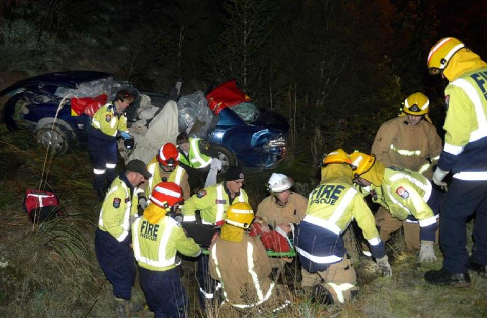 Firefighters help free a female passenger after the car she was in hit black ice yesterday. Photo...