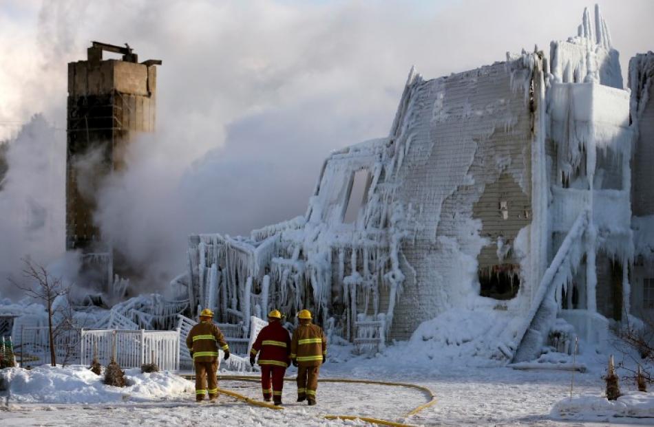 Firefighters walk past the Residence du Havre after the fire. REUTERS/Mathieu Belanger