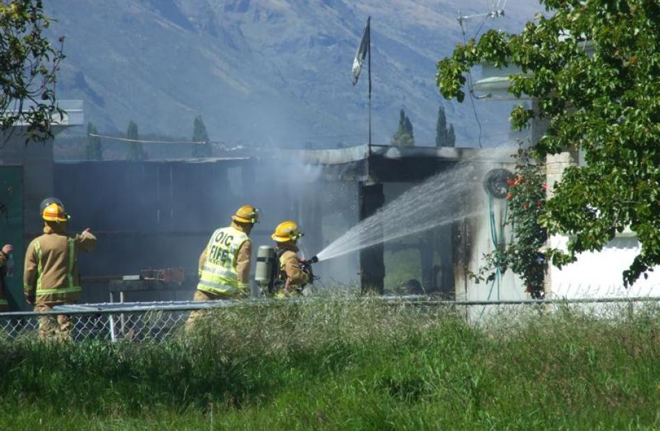 Firefighters work to put out a shed fire in Frankton yesterday. Photo by Christina McDonald.