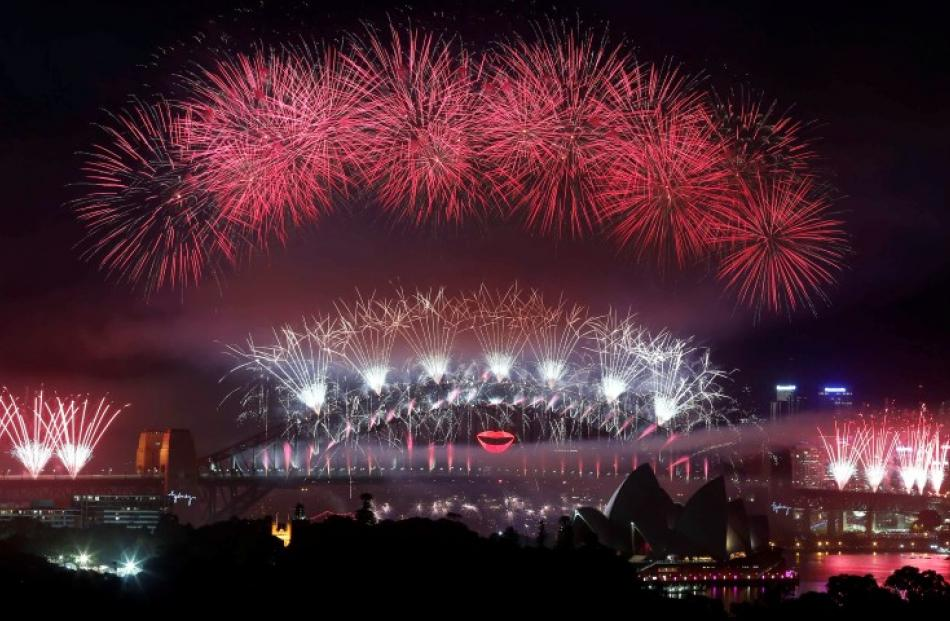 Fireworks explode over and around the Sydney Harbour Bridge and Sydney Opera House during new...