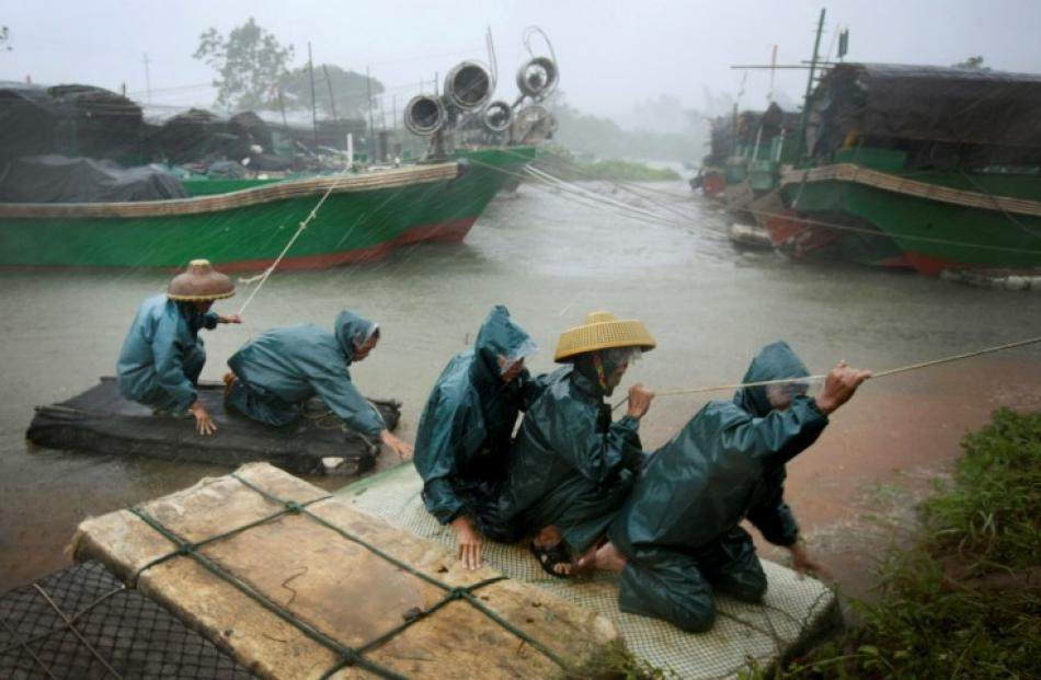 Fishermen are transported to a safer area amid strong wind and heavy rainfall at a port as...