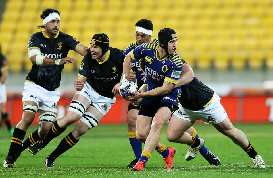 Fletcher Smith of Otago looks to offload during the ITM Cup semifinal between Wellington and...