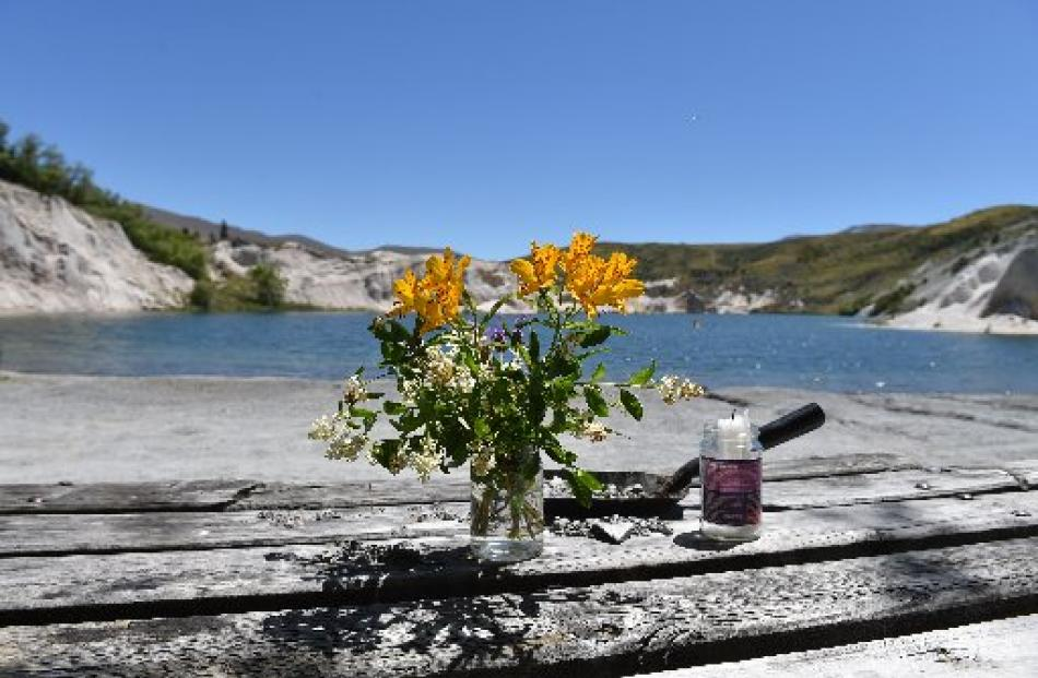 Flowers and a candle on a picnic table with the Blue Lake in the background. Photo by Staff...
