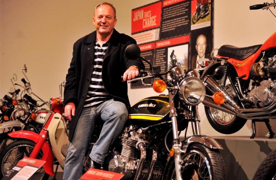 Former international motorcycle racer Graeme  Crosby (58) takes a closer look at a 1974 Kawasaki...