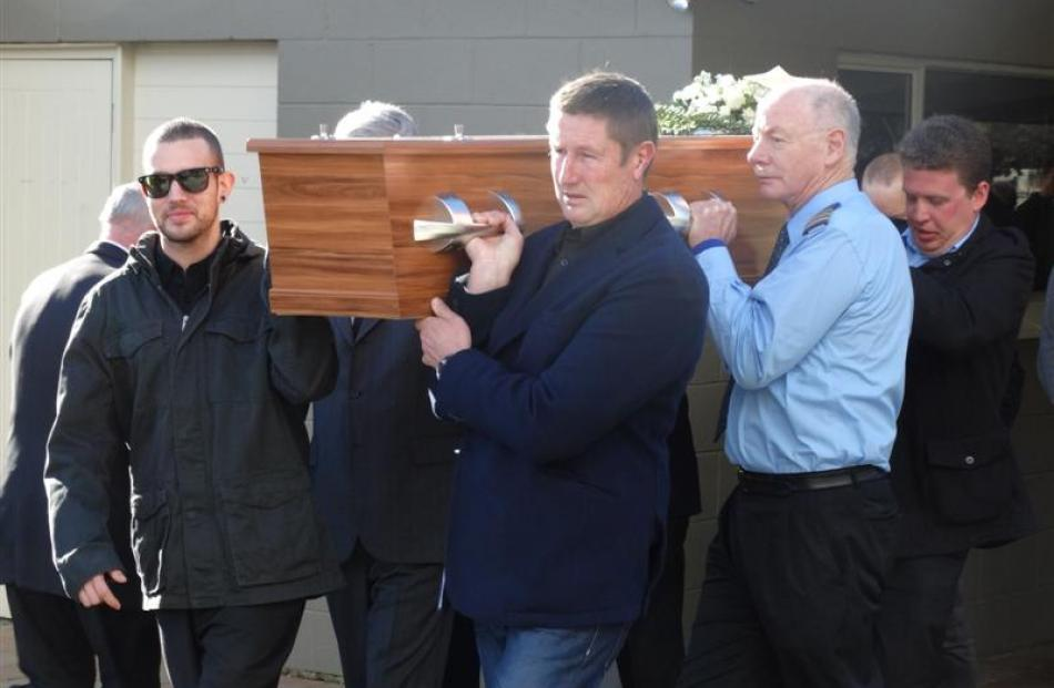 Friends and family carry the casket of Glenorchy Air senior pilot Ray Crow after a funeral...