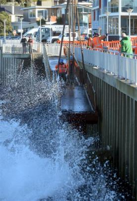 Fulton Hogan contractors use a crane to remove a damaged section of ramp from the Esplanade at St...