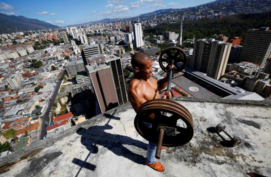Gabriel Rivas lifts weights on a balcony on the 28th floor of the 'Tower of David' skyscraper in...