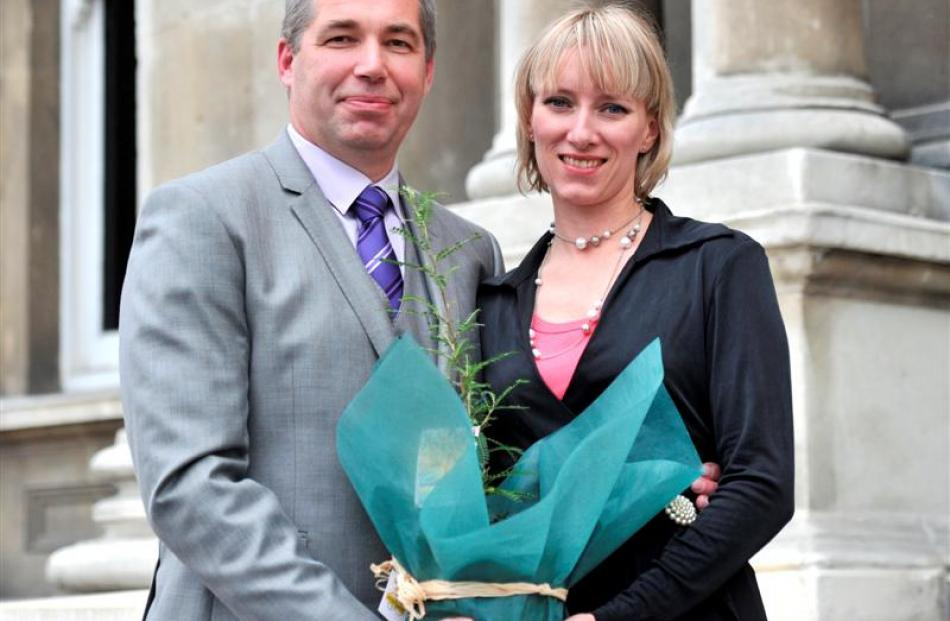 Gennadiy Labara (48) and Maryna Bilousova (37), originally of Ukraine, hold the kowhai plant...