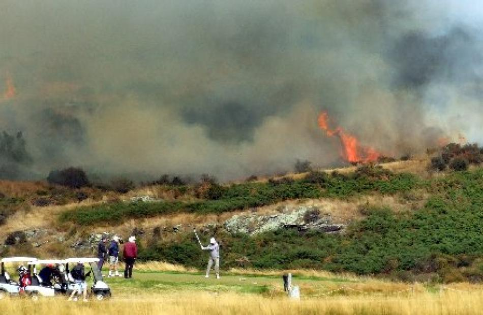 Golfers tee off while the fire rages in the background.
