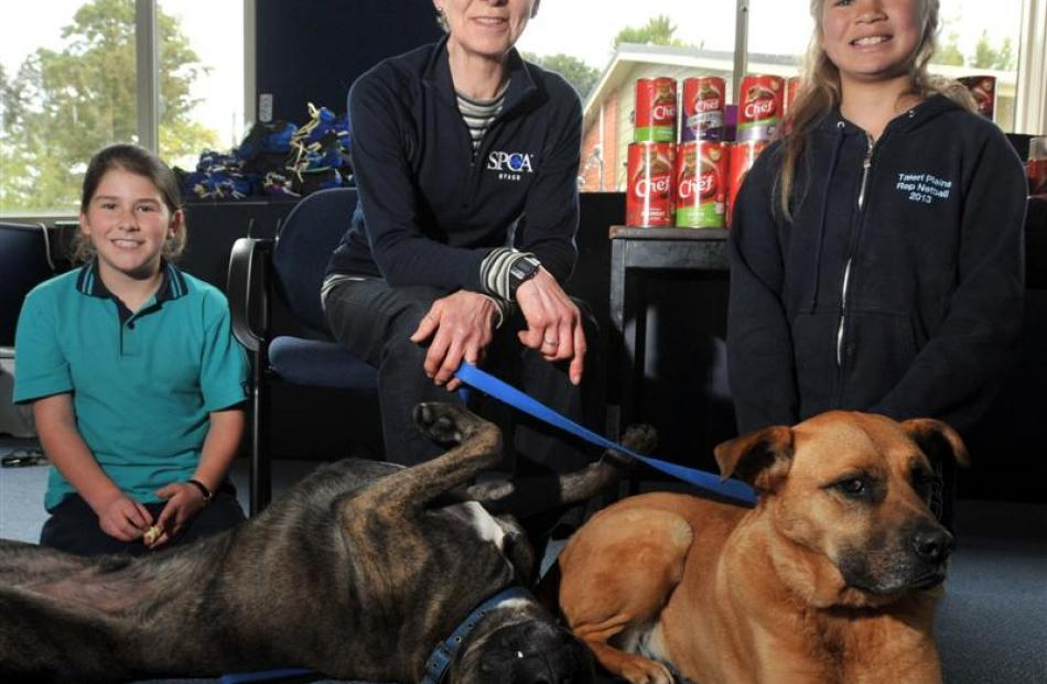 Grace Cotter (9, left), and Olivia Fowler (10) with Marjorie Orr,  of the  Otago SPCA, dogs Kudos...