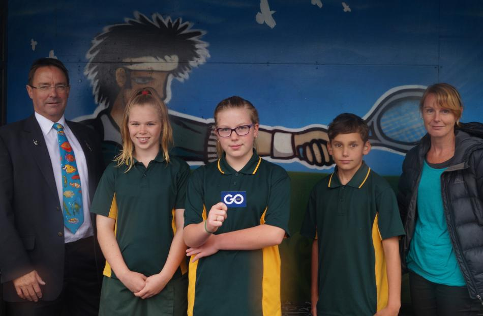 Green Island School pupil Lily Reid (12, centre) holds a Go bus card with (from left) Green...