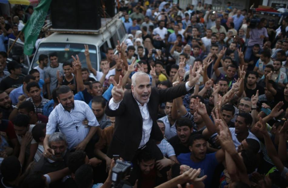 Hamas spokesman Fawzi Barhoum (C) is carried by Palestinians as they celebrate what they said was...