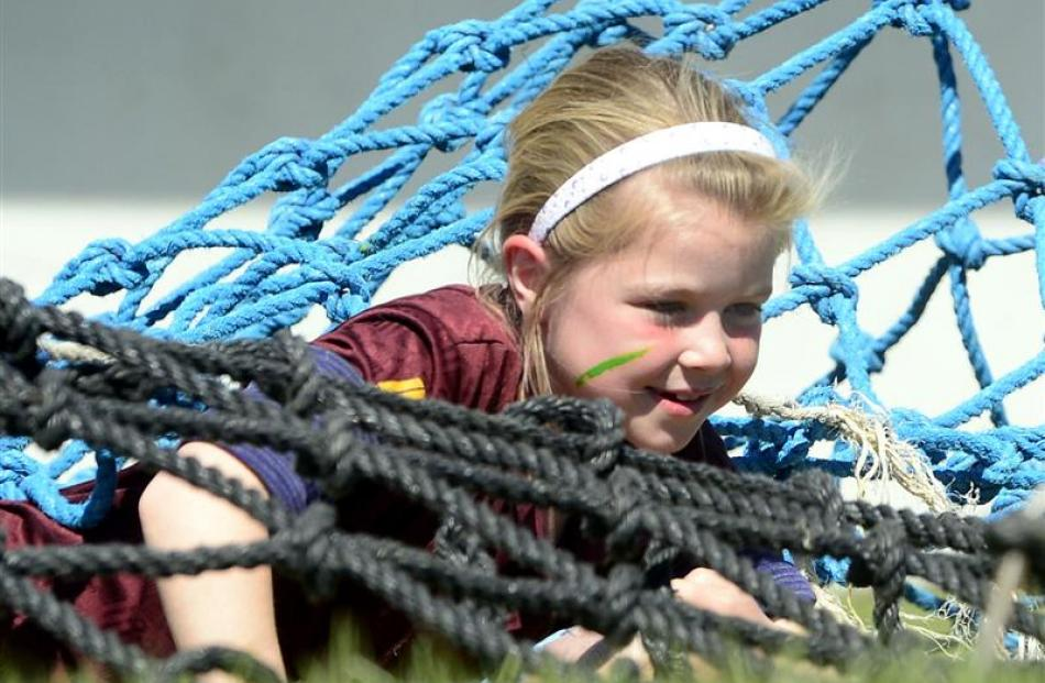 Hannah Murray (8), of Waitahuna School, crawls under a net during the obstacle race in the sports...