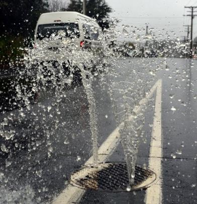 Heavy rain causes water to squirt out of a manhole in Barr St yesterday.