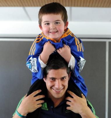 Highlanders midfield back Phil Burleigh with Brody Clark, of Dunedin, yesterday. Brody models  a ...