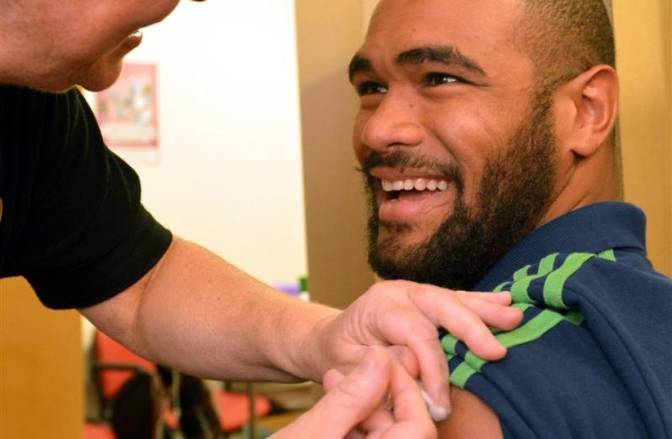 Highlanders winger Patrick Osborne gets a flu vaccination from Stephanie Pomfret at Dunedin...
