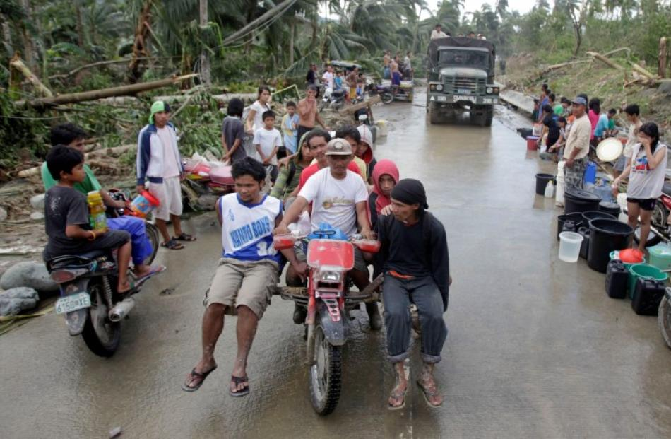 Homeless typhoon victims are transported on a motorcycle after Typhoon Bopha hit Compostela...