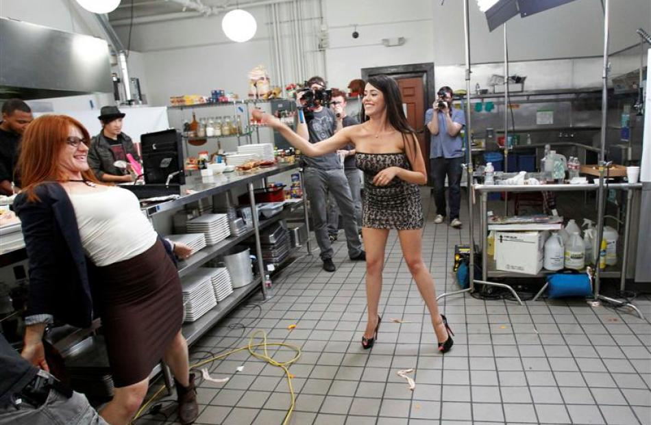 Hostess Kayla Leon throws bacon at judge Andie Bolt during the taping of Epic Chef Episode 5:...