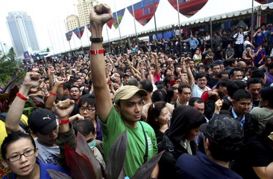 Impatient Indonesians raise their fists to show their 'priority' wrist bands as they queue up to...