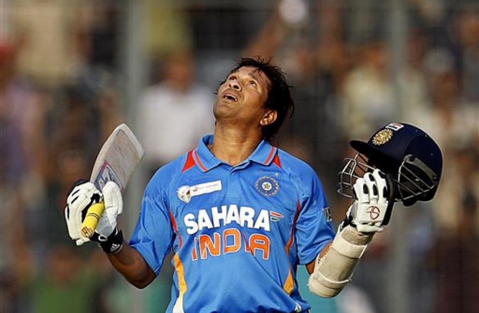 Indian batsman Sachin Tendulkar celebrates scoring his 100th international century during the...