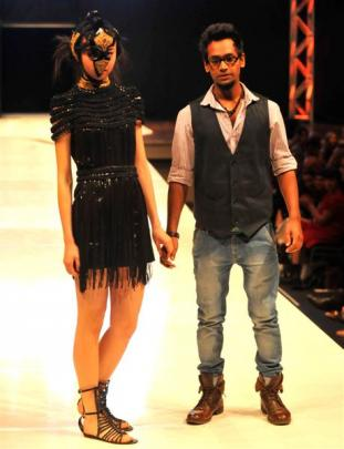 Indian designer Vaibhav Singh walks the runway with a model in one of his creations, after being...
