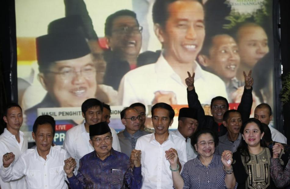 "Indonesian presidential candidate Joko ""Jokowi"" Widodo (centre) and his running mate Jusuf Kalla ..."