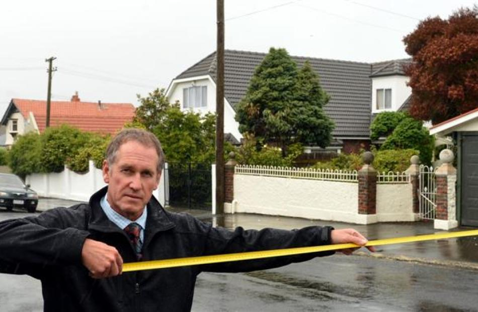 Ings Ave, St Clair, resident Wayne McFarlane shows with a tape measure how far the Dunedin City...